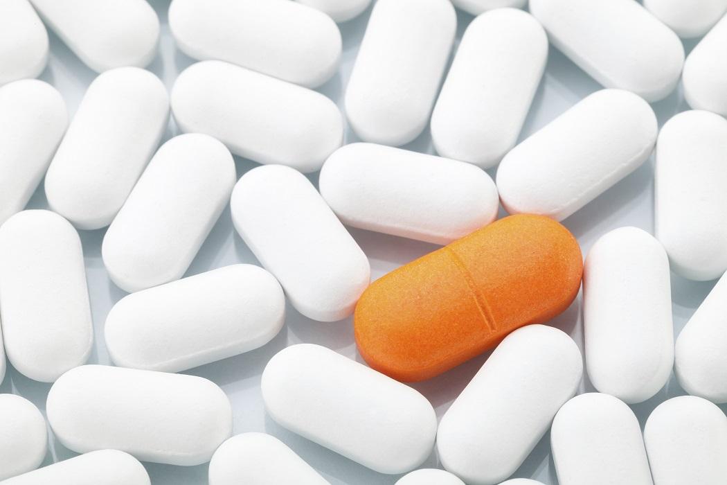 Orange pill between white ones